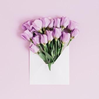 Красивые фиолетовые цветы eustoma в конверте на розовом фоне