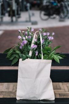 美しい紫のeustomaの花と白い綿のハンドバッグ