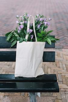 黒いベンチで美しい紫のeustomaの花と白い綿のハンドバッグ