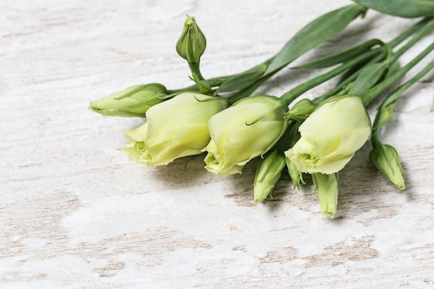 Eustoma свежих белых цветков на деревянном столе с космосом экземпляра. молодые нежные цветочные бутоны.