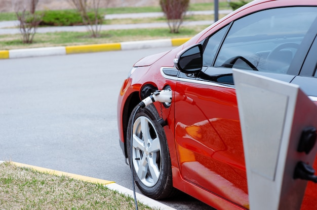 Ev car или electric красный автомобиль на зарядной станции с кабелем питания