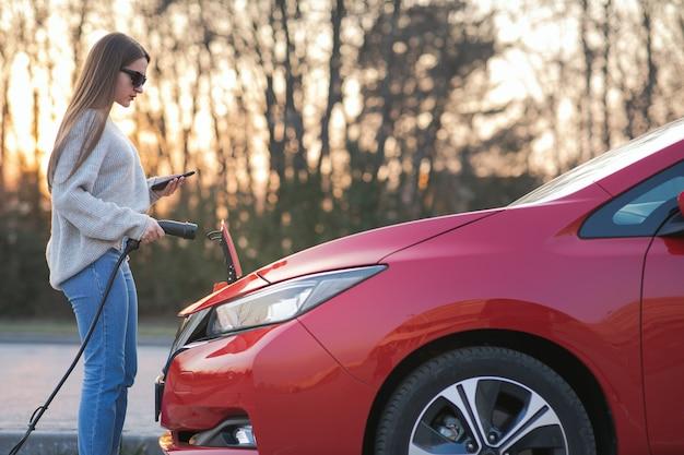 Девушка затыкает электромобиль для зарядки автомобильного аккумулятора на стоянке. подсоединен зарядный кабель электромобиля. ev парковка, кабель зарядного устройства, зарядная станция