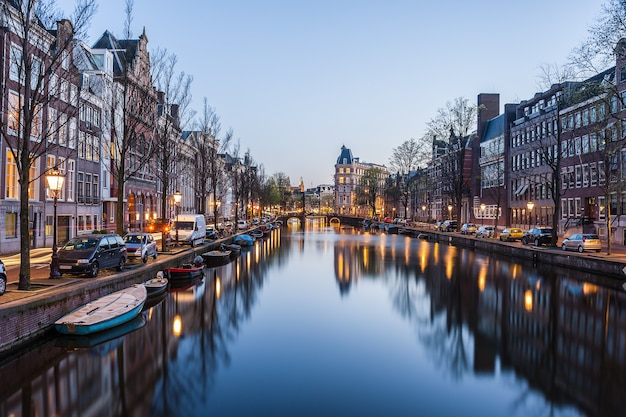 Evening in amsterdam, night cityscape with buildings and river
