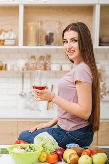 家での夜。アルコールリラクゼーション。キッチンカウンターに座っている赤ワイングラスを持つ美しい若い女性。