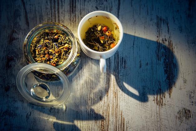 拡散光の中でハーブ、花、ベリー、松の実から作られたイブニングブレンドティー。マグカップとガラスのボウルのお茶、灰色の木製テーブルの影。漢方薬、健康増進、減量。