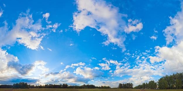 平野と森のキャンプの上の雲と夕方の青い空のパノラマ。セブンショットステッチ画像。