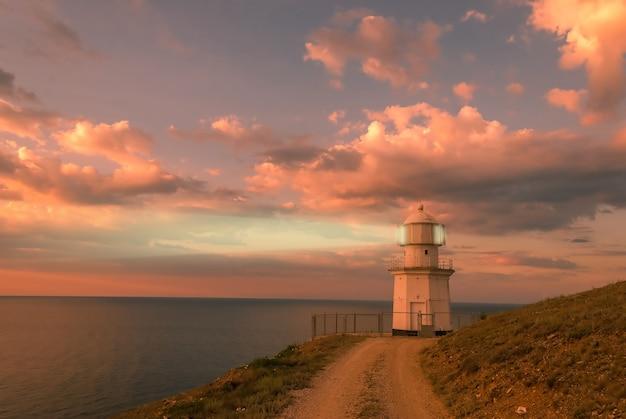 Вечерний пейзаж с маяком на берегу моря, луч света в сумерках для мореплавателей, драматический морской пейзаж