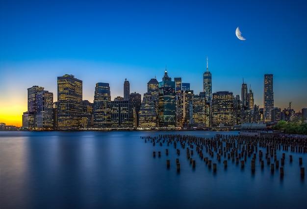 夜のマンハッタンの高層ビルと反射のある水