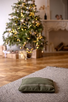 Evening new year's interior with soft green pillow on the floor, foreground and christmas tree with glowing garlands and white fireplace in the background. vertical