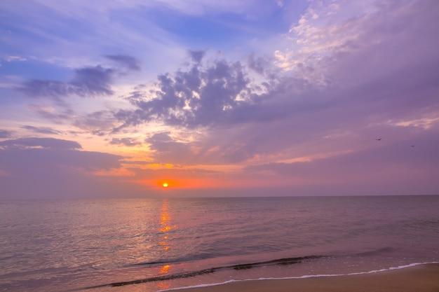Вечер на пляже спокойного бескрайнего моря. разноцветный закат и облака