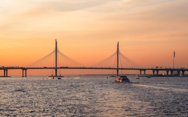 サンクトペテルブルクのネヴァ川水域の夕方のパノラマ。小さな斜張橋。