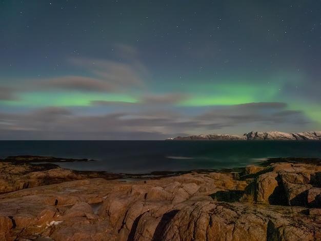 Evening polar landscape with the aurora borealis.