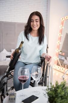 Вечерний отдых. веселая женщина-инвалид улыбается и наливает вино