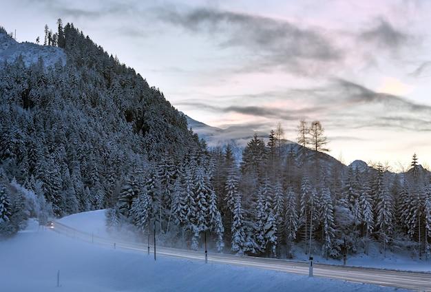 저녁 도로, 겨울 눈 덮인 전나무 숲과 산이 시작되었습니다.