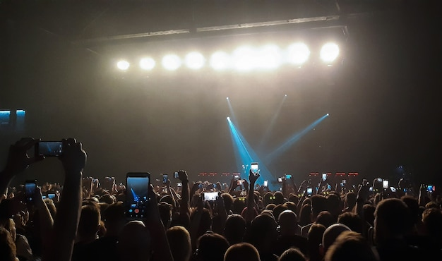 An evening rock concert in front of a large audience in a club filming on mobile phones