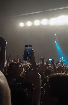 An evening rock concert in front of a large audience in a club with shooting on a mobile phone
