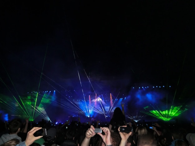 An evening rock concert in front of a large audience at an open-air stadium with a laser show