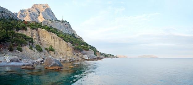夕方の岩の多い海岸線のパノラマと斜面の古い灯台