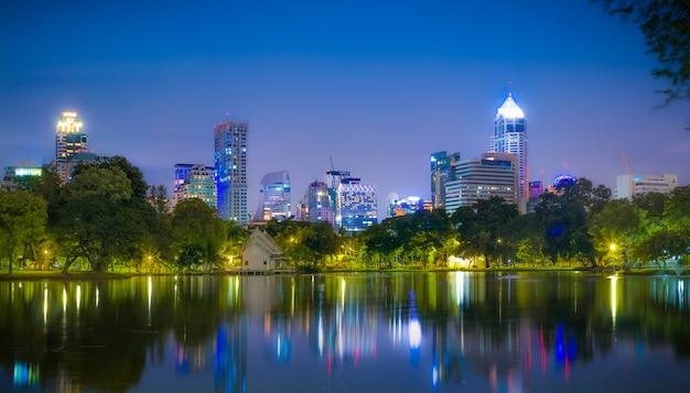 Evening scene of bangkok skyline at lumphini park in bangkok.