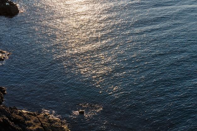 水面に太陽が反射する夜の海の岩の多い海岸ビュー。