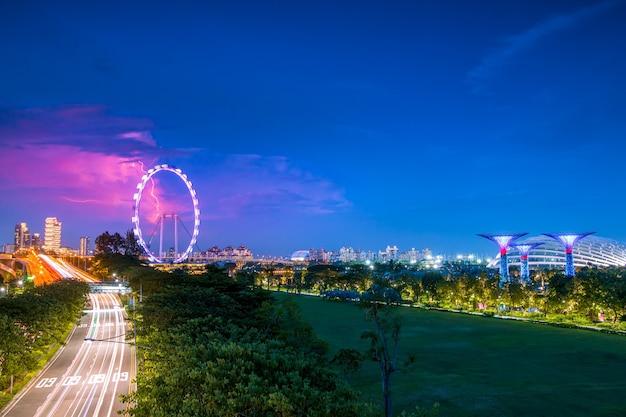 저녁 싱가포르. 도로 교통, 가든스 바이 베이의 슈퍼 트리 및 싱가포르 플라이어 위의 번개