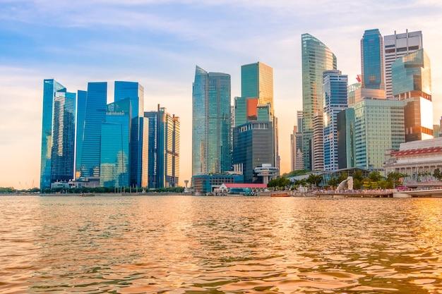 イブニングシンガポール。マリーナベイの海岸にある高層ビル。太陽が水を金色に染めた