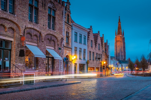 Evening on the streets of bruges after the rain. view of the night onze lieve. vrouw brugge against the background of a blue evening sky. belgium.
