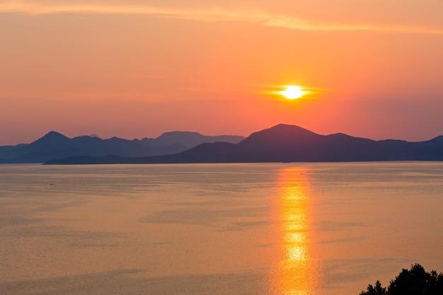 Вечернее побережье летом с розово-желтым закатом, солнечной дорожкой и островом на горизонте. вид с полуострова пелешац (хорватия)