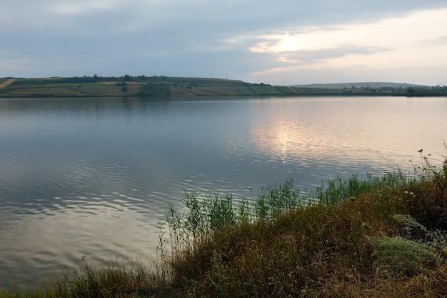 水面に太陽が反射する夏の夜の湖の風景。
