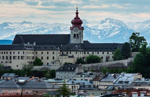 저녁 여름 잘츠부르크시 (오스트리아)는 논 베르크 수도원 베네딕토 회 수도원 (1880 년대 바로크 양식으로 개조) abd 알프스 산에서 위로 볼 수 있습니다.