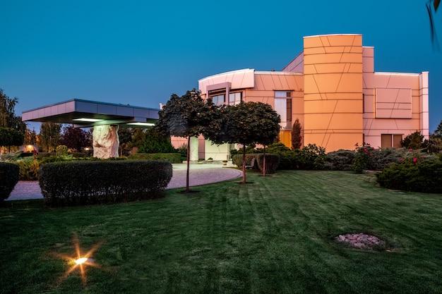 현대 맨션 주변에 조명과 식물이 있는 잘 손질된 잔디의 여름 저녁 전망