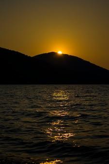 Вечерний закат за горой на большом озере романтический вид на закат на озере среди ...