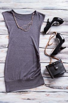 Evening top with black heels. gray top and chain necklace. designer clothes on boutique showcase. dark colors of charm.