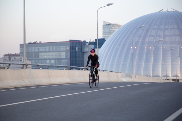 Evening training of a female cyclist in the city