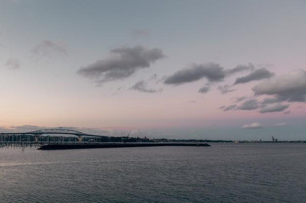 Вечерний вид на оклендский мост и спокойную воду гавани