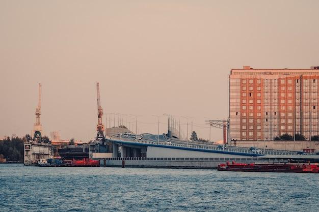 高架橋を通過する交通量のあるサンクトペテルブルクの夜景。工業企業の造船会社almazの造船所。ロシア。