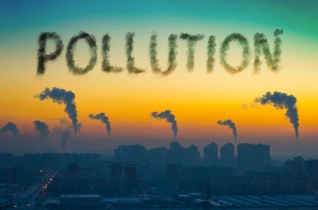 日没時に煙突から煙が放出される街の産業景観の夜景。碑文の汚染。