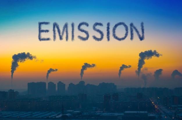 日没時に煙突から煙が放出される街の産業景観の夜景。