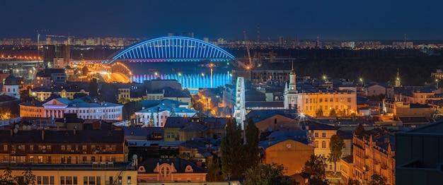 Вечерний вид на подольский мост, днепр и колесо обозрения