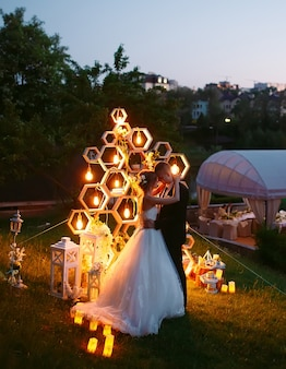 Evening wedding ceremony. the bride and groom are on the background of the wedding arch.