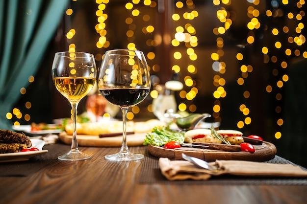 Вечерний винный праздничный ужин на размытых огнях Premium Фотографии
