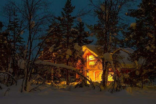 夕方の冬の森。大きな雪の帽子で覆われた枝。バックグラウンドで照明付きのコテージ