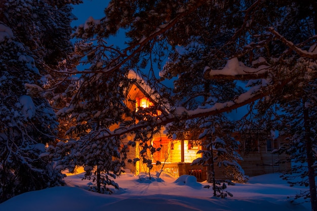 Evening winter forest. pine branches covered with large caps of snow. lighted cottage in the background