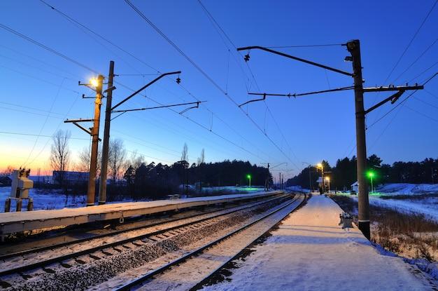 燃えるセマフォとランタンのある鉄道の夜の冬の風景。長い道のりと田舎のコンセプト。町の概念からの旅行