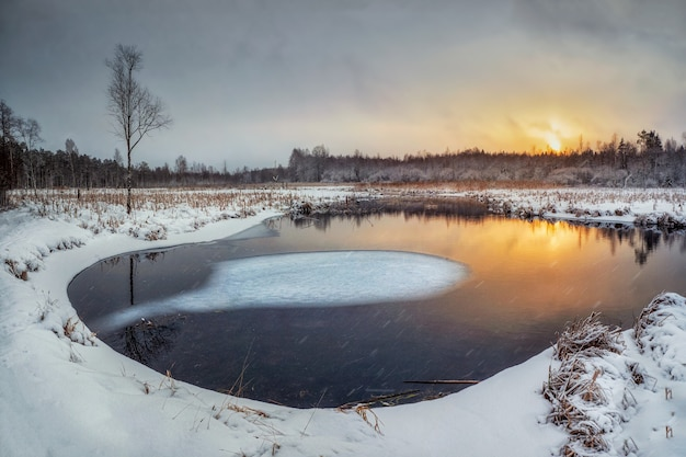 Evening winter sunny sunset landscape with backwater and ice on the river.