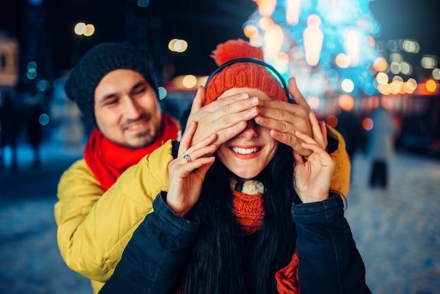 Вечерняя зимняя прогулка, влюбленная пара играет на площади в угадай, кто. мужчина и женщина, имеющие романтическую встречу на городской улице с огнями