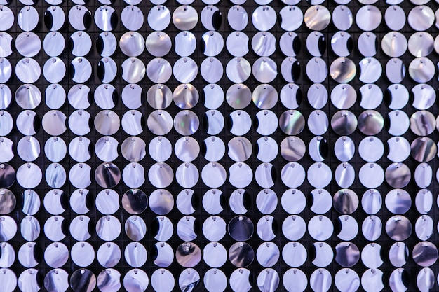 Event decoration on photo zone. press wall made of many round sparkling sequins. bright abstract background of bestirring tinsel