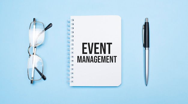Event management words in white notepad, pen and glasses on blue background. concept