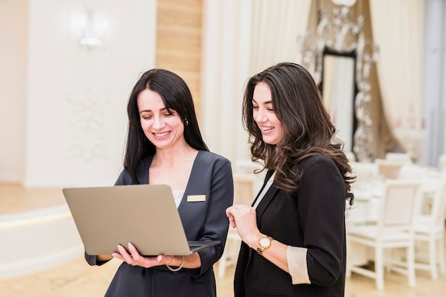 Event manager showing laptop to happy woman