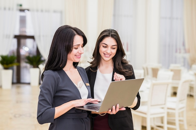 Event manager showing on laptop to young woman